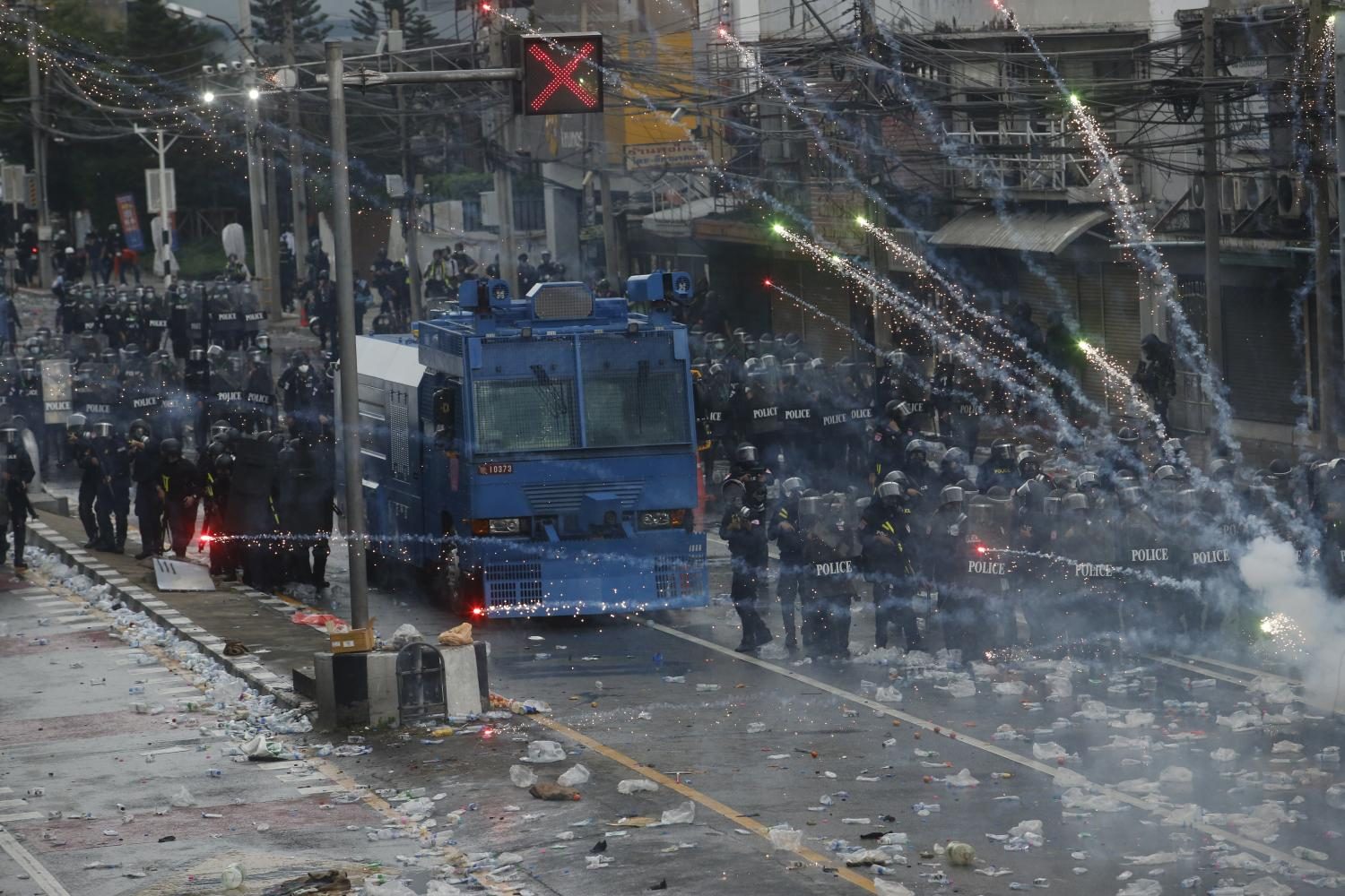 ON COURSE FOR COLLISION: Flares are launched near police during the confrontation between a water cannon truck and protesters near Din Daeng intersection.