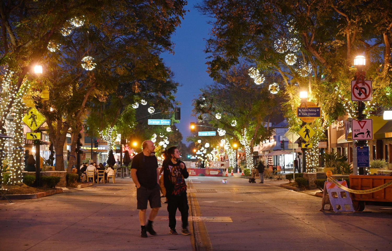 Two people walk down the main shopping and dining street in Burbank, California, closed to vehicular traffic to allow restaurants to serve food outside during the coronavirus pandemic.(Photo: AFP)