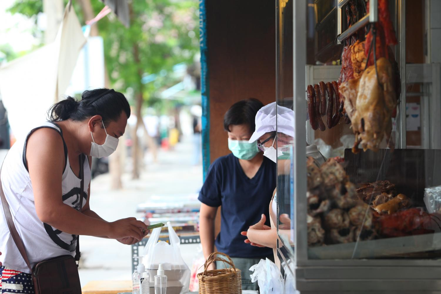 People make daily food purchases in the Ratchawat market during the pandemic.(Photo: Apichart Jinakul)