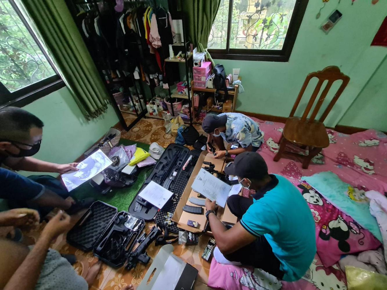 Plainclothes police search a house in Nakhon Si Thammarat where they found several firearms. The officers examined gun possession documents held by the owner. photos by the CSD