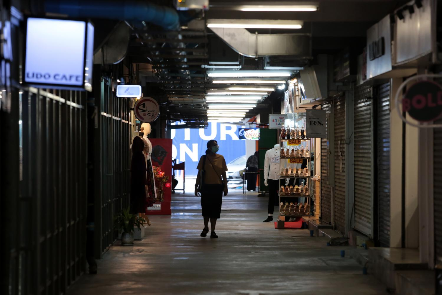 A woman looks at closed stores while walking alone in Siam Square in Pathumwan district.(Photo: Chanat Katanyu)
