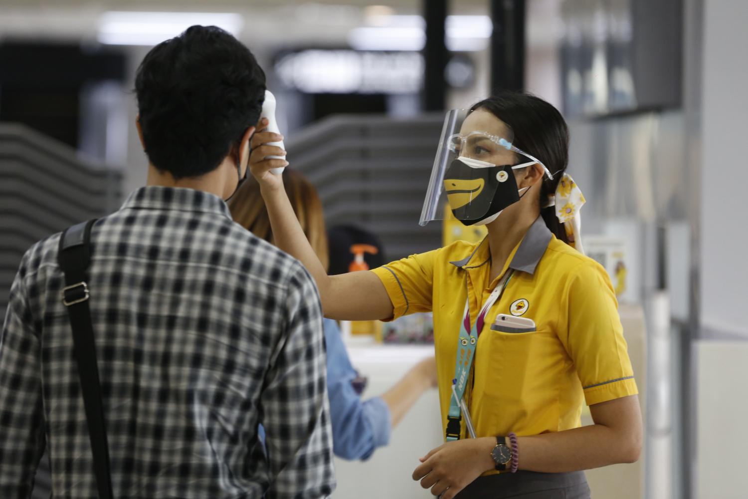 A Nok Air crew member screens passengers during check-in at Don Mueang airport.