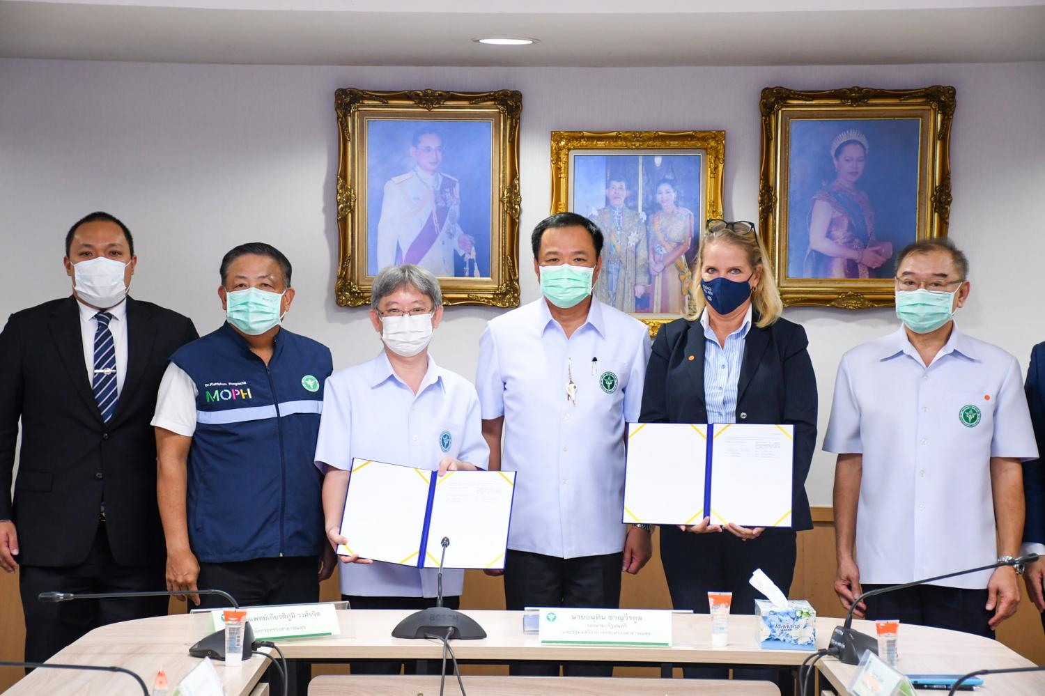 Public Health Minister Anutin Charnvirakul, centre, with other officials, and Dr Opas Karnkawinpong and Pfizer's Deborah Seifert holding signed purchase contracts yesterday.(Public health Ministry photo)