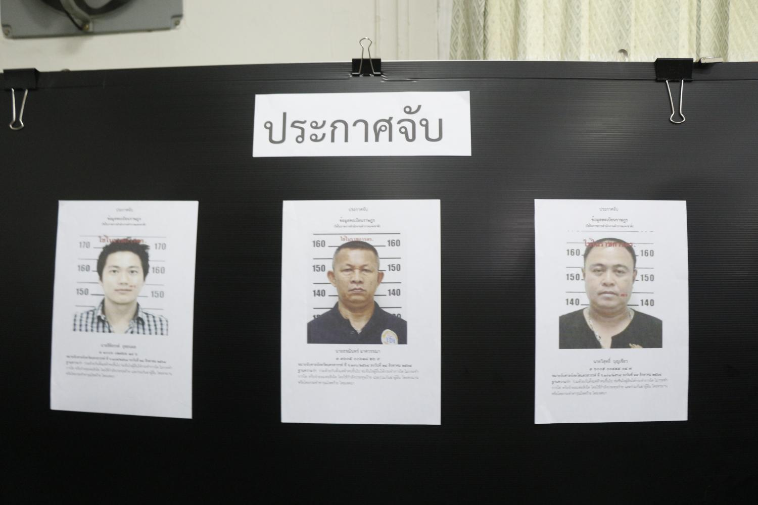 A copy of the warrant for the arrest of Pol Col Thitisan Utthanaphon, left, is posted along with those for other suspects on a notice board displayed during a press conference in Nakhon Sawan yesterday.(Photo: Chalit Phumruang)