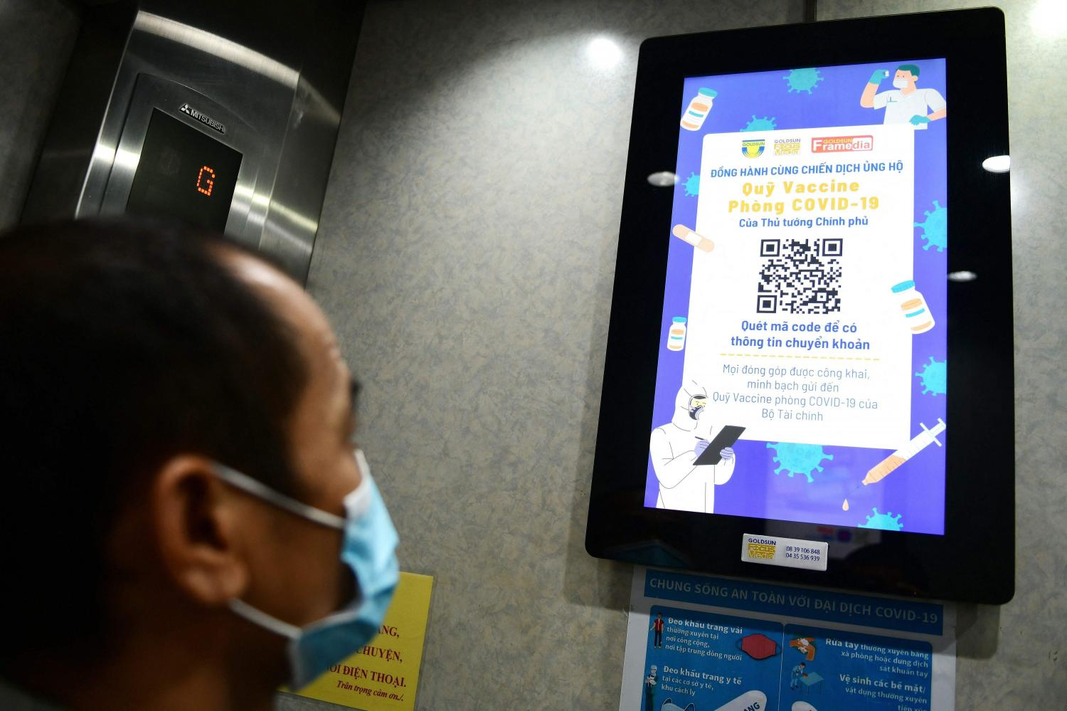 A man looks at a display screen in an elevator asking for public donations to Vietnam's national fund for a Covid-19 vaccine in Hanoi on June 8, as the country struggles to contain a new virus wave.(Photo: AFP)