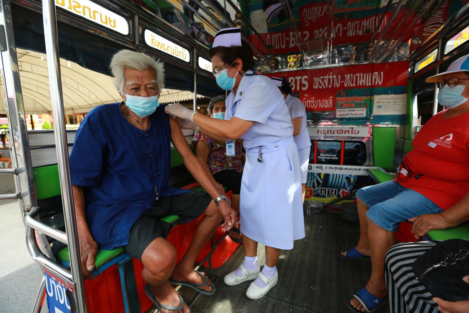 Nurses in a mobile vaccine van provide Covid shots to the elderly in Wat Bang Phli Yai in Bang Phli district of Samut Prakan. The Covid situation is improving after a dip in cases and more vaccinations.(Photo: Somchai Poomlard)