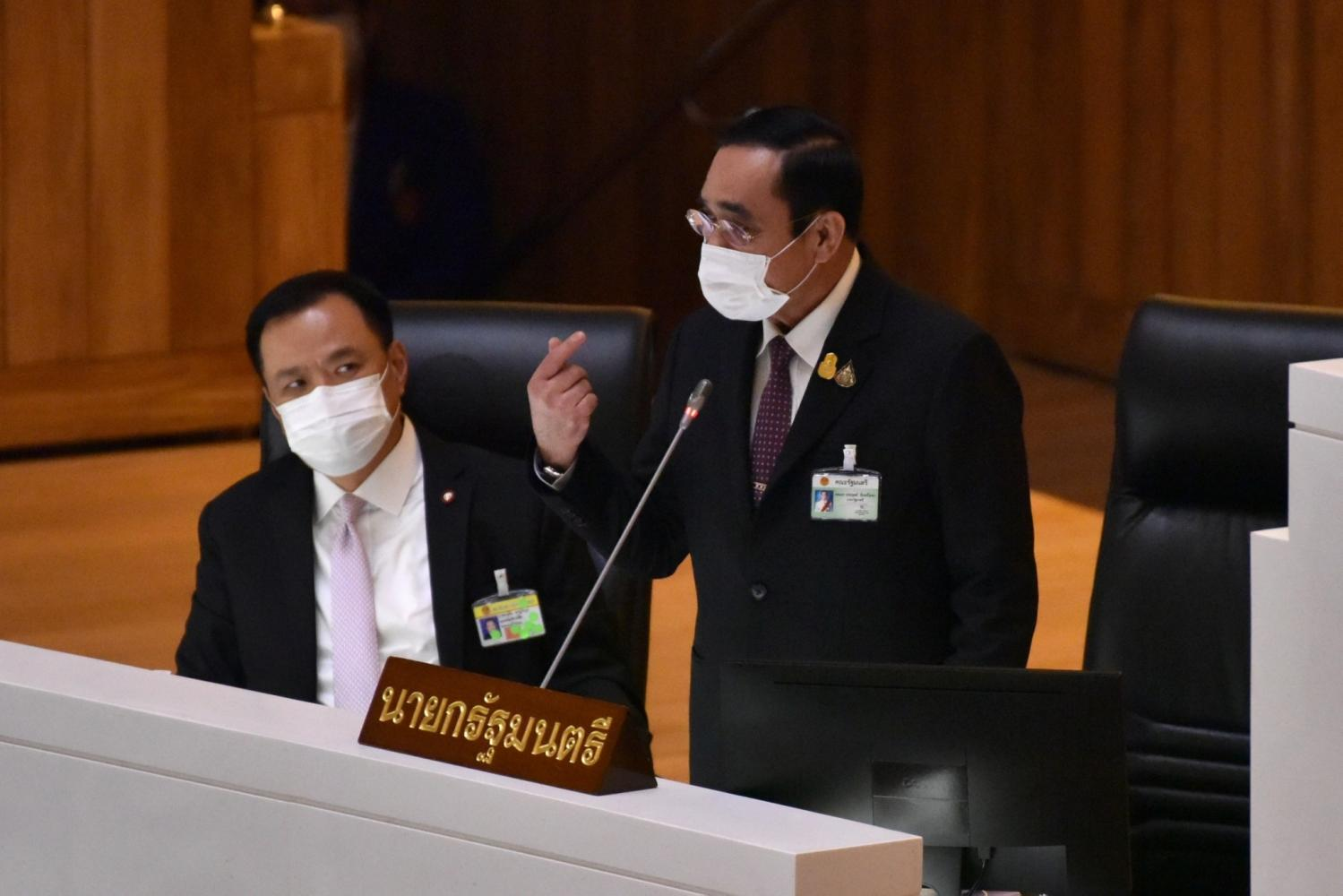 PM Prayut Chan-o-cha makes a point during his rebuttal of the censure debate allegations against him in parliament. The four-day no-confidence debate began on Tuesday targeting Gen Prayut and five other cabinet members including Deputy Prime Minister and Public Health Minister Anutin Charnvirakul (left).(Parliament photo)