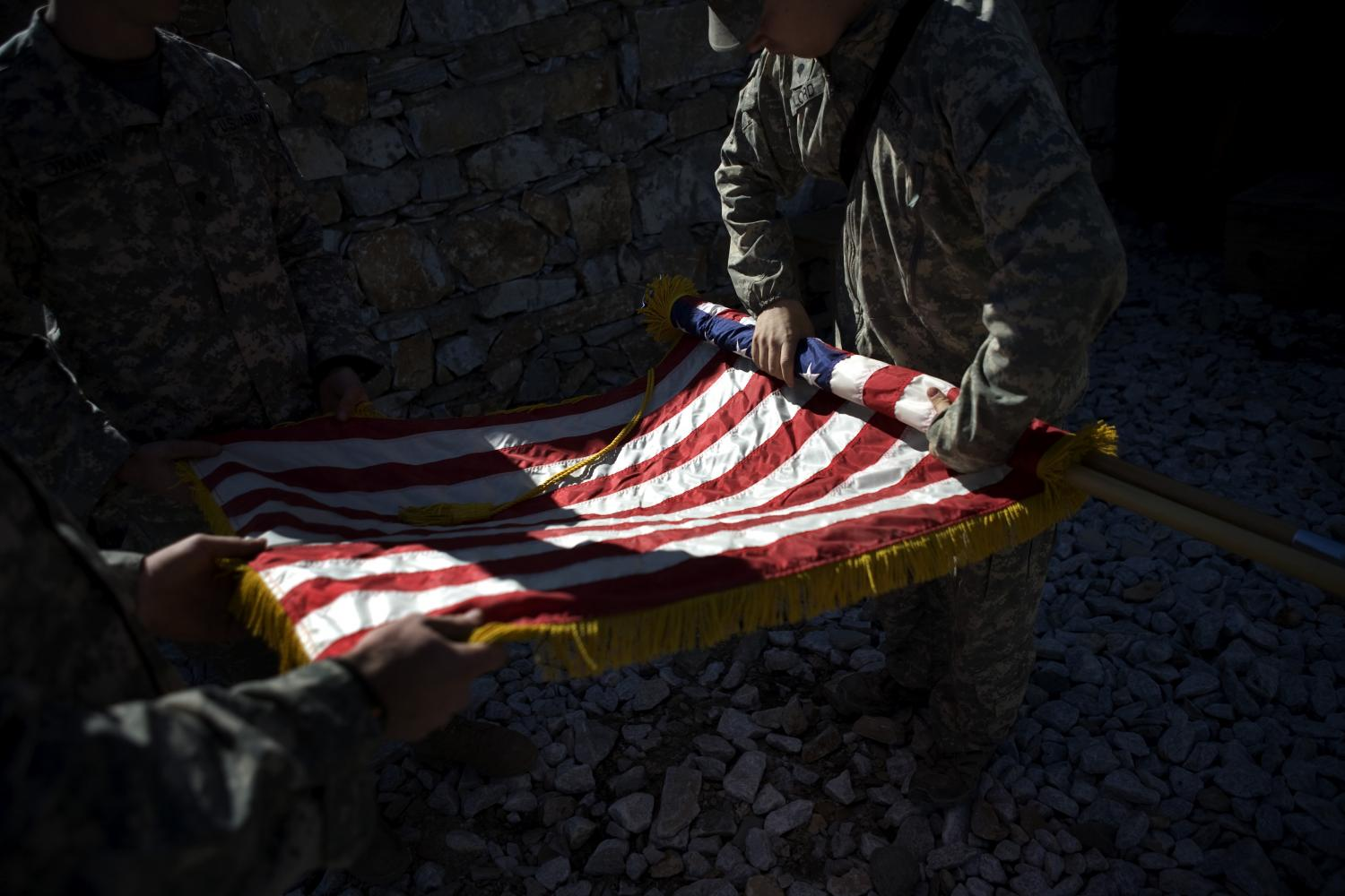 US soldiers take down a flag after a memorial service for a fallen comrade in Afghanistan's Kunar province on April 23, 2009. The last American flight from Afghanistan on Monday left behind a host of unfulfilled promises and anxious questions about the country's fate.(Photo: NYT)