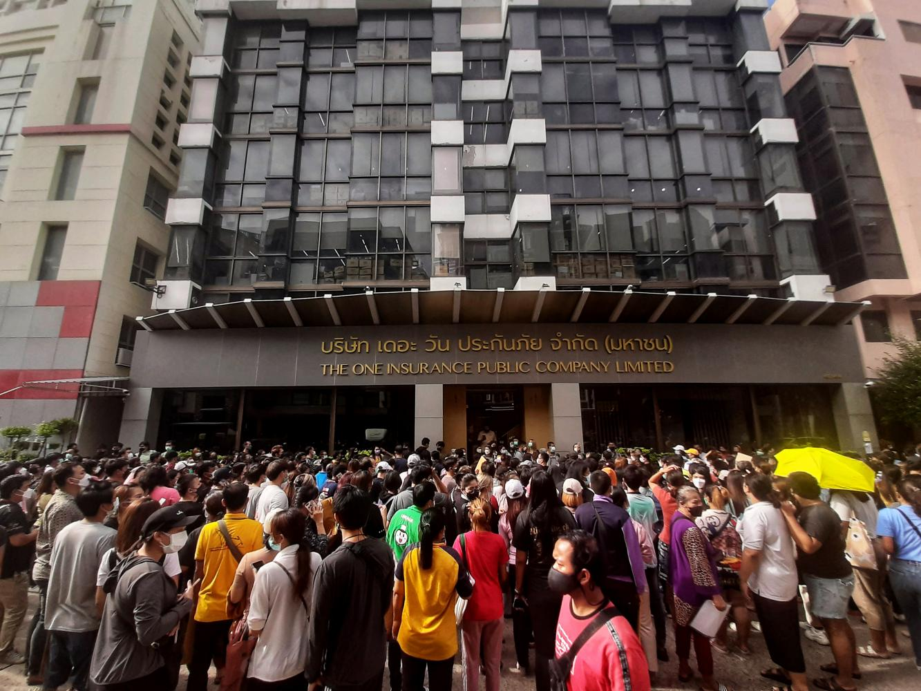 Around 500 people gather in front of The One Insurance Plc on Monday to push for speedier claims reimbursement for Covid-19 insurance. ARNUN CHOLMAHATRAKOOL