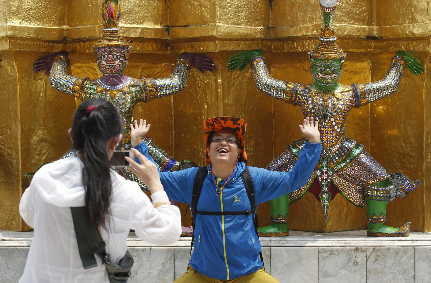A Chinese tourist strikes a similar pose to statues as they visit the Grand Palace in Bangkok. In 2019, before the coronavirus hit Thailand and the rest of the world, nearly 11 million tourists from China came to Thailand — or almost a third of foreign tourists.(Photo: Chaiwat Subprasom)