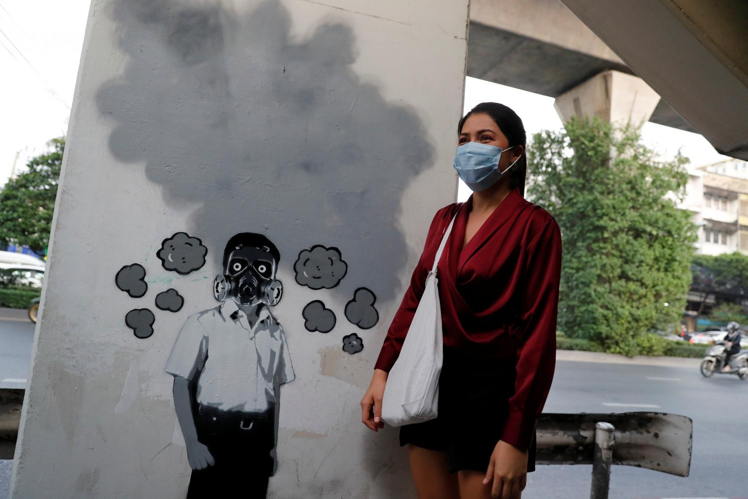 A pedestrian poses next to a graffito by Thai artist Headache Stencil which references the poor air quality in Bangkok. Thais have been living with air pollution, PM2.5 particles, and have worn N95 masks years before Covid-19 arrived.(Photo: Reuters)
