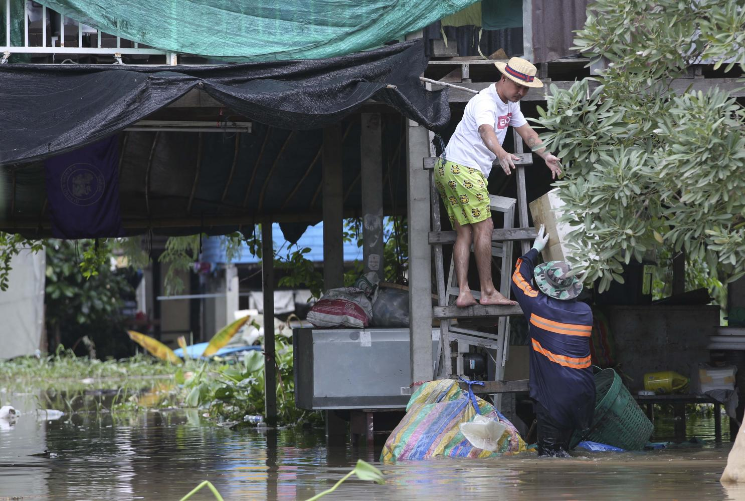 Rising damp: People living along the Chao Phraya River in Pathum Thani's Sam Khok district move their belongings to a higher floor after the area was flooded.