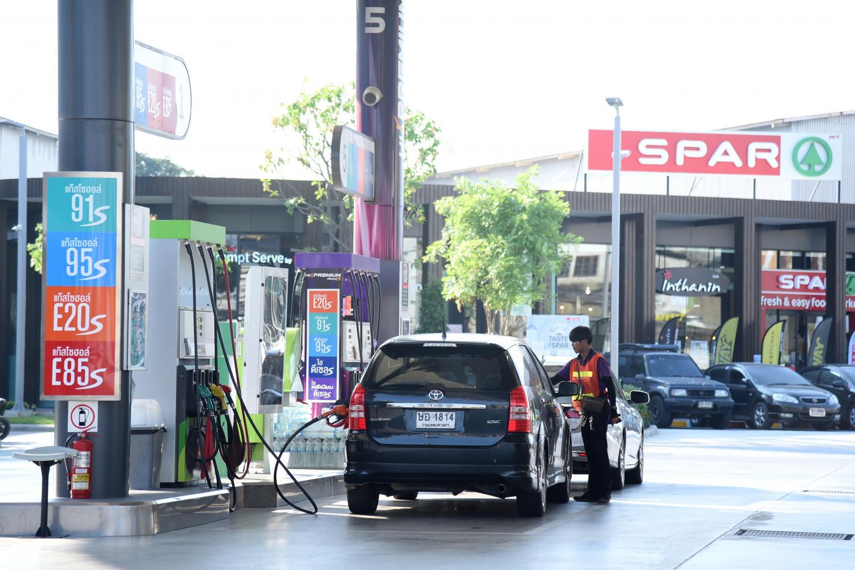 An attendant fills a customer's tank at a Bangchak petrol station.