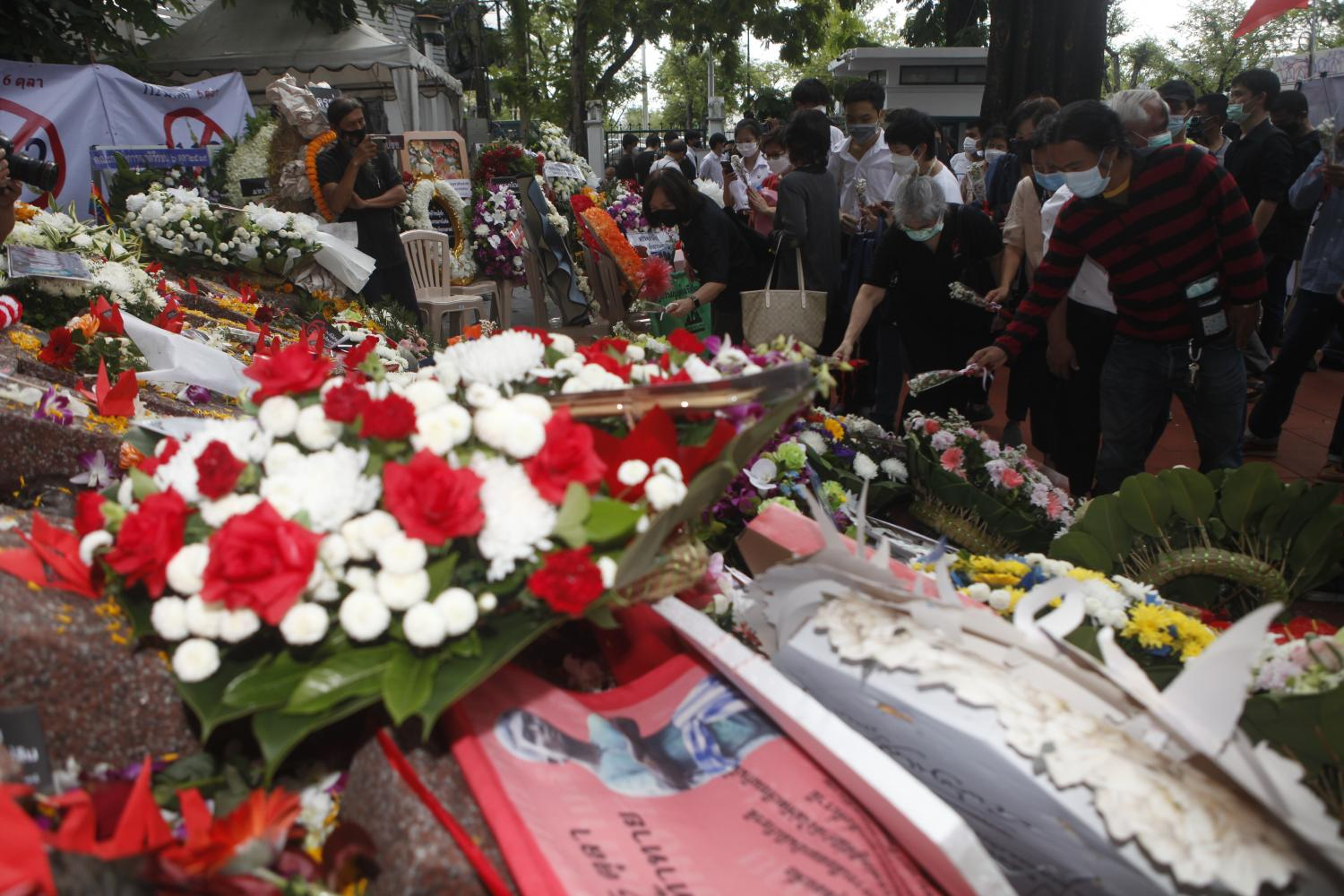 People lay wreaths and flowers in remembrance of the Oct 6, 1976 massacre, during the memorial gathering at Thammasat University, Tha Prachan campus, on Wednesday. (Photo: Nutthawat Wicheanbut)