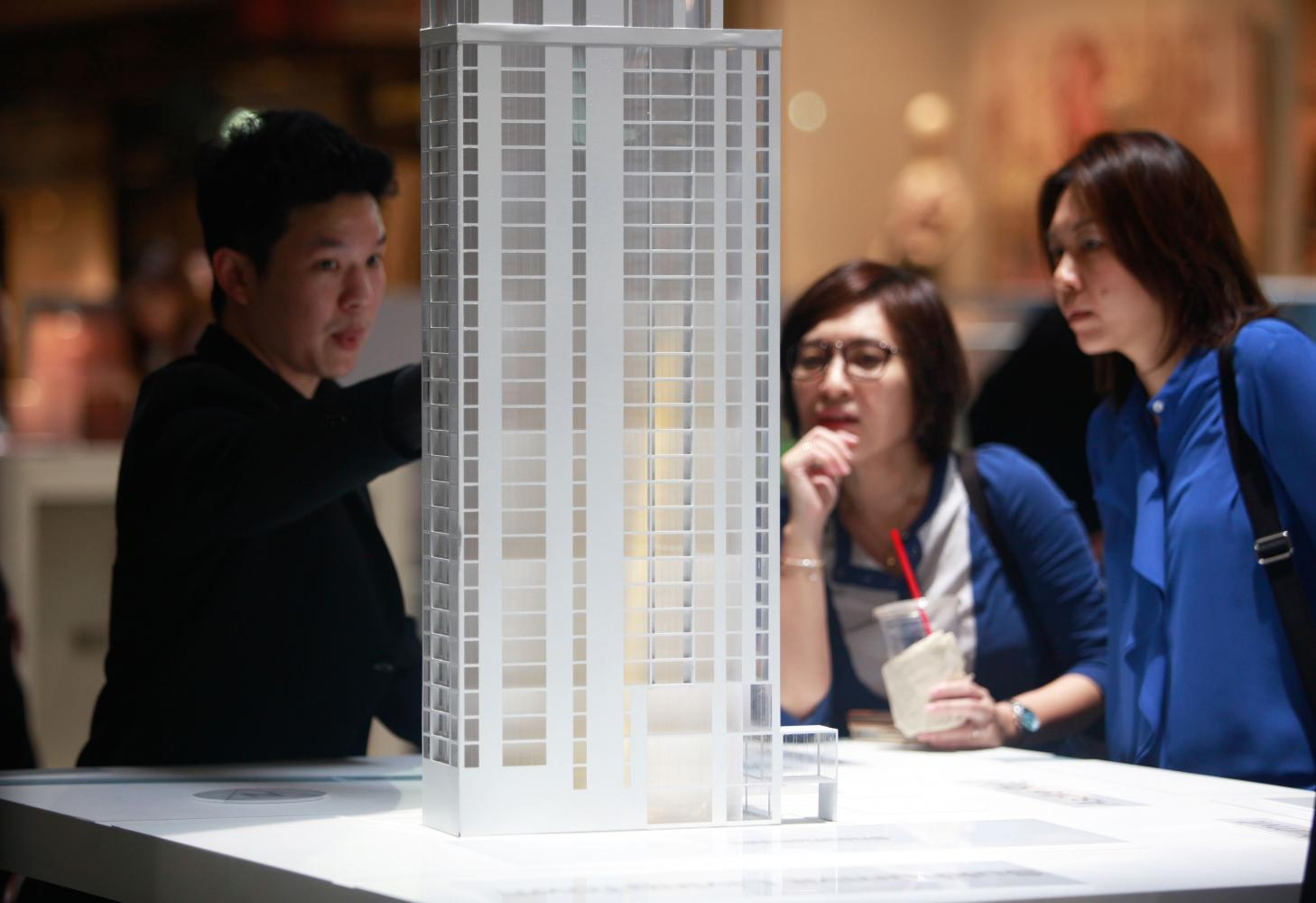 People check out the details of a luxury condominium project at a property fair in Bangkok.